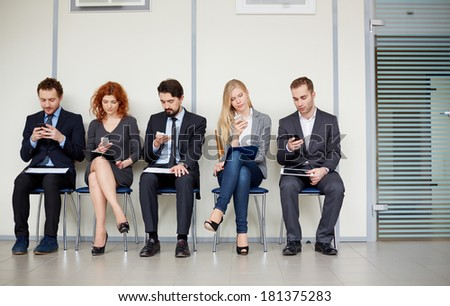 Row of several business partners using their mobile phones - stock photo