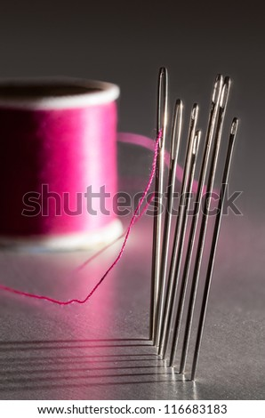 Row of sewing embroidery needles with red thread and shadows with bobbin - stock photo