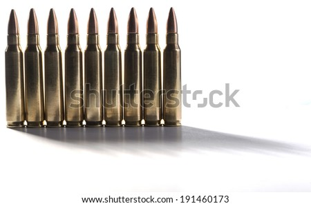 Row of shiny rifle bullets standing together isolated on white with shadows - stock photo