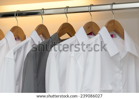 row of shirts hanging on coat hanger in white wardrobe - stock photo