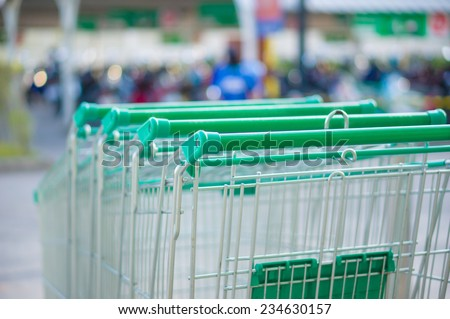 Row of shopping cart with green handles on parking near supermarket - stock photo