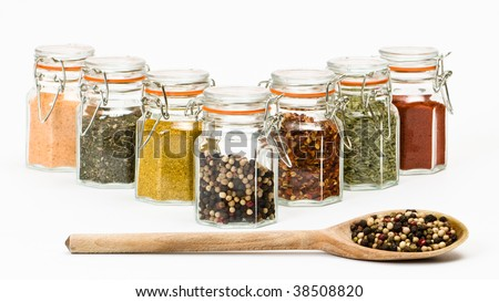 Row of spice jars with wooden spoon full of peppercorns on white background - stock photo