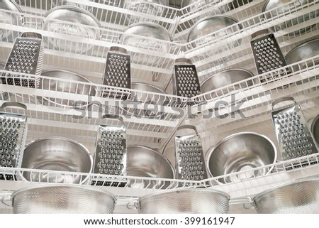 row of stainless kitchenware on a shelf - stock photo