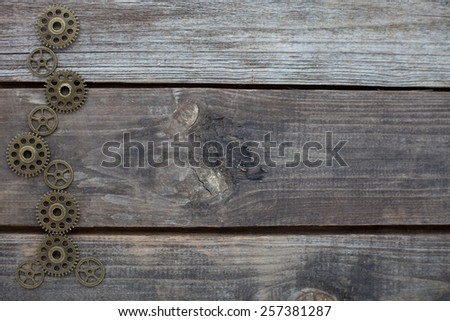 row of steampunk gears on a wooden background - stock photo