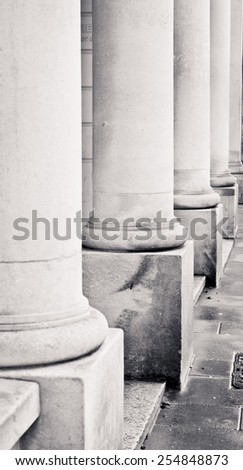 Row of stone pillars on the outside of an urban building in black and white - stock photo