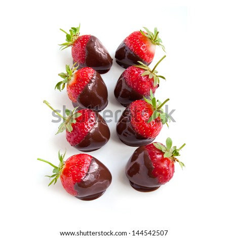 Row of strawberries dipped in delicious chocolate isolated on the white background - stock photo