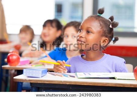 Row of students in a primary interracial classroom. Afro american girl paying attention to the teacher. - stock photo