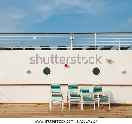 row of sun chairs  on the ship deck - stock photo