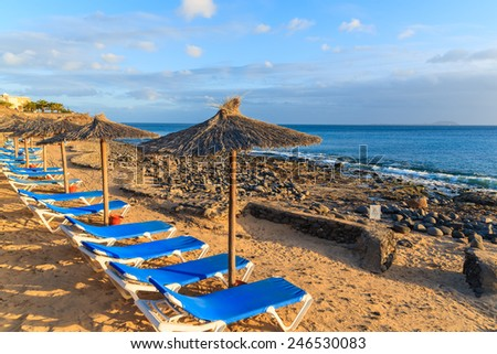 Row of sunbeds and umbrellas on Playa Blanca beach at sunset time, Lanzarote, Canary Islands, Spain - stock photo