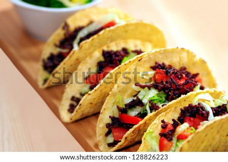 Row of taco shells on wooden plank - stock photo