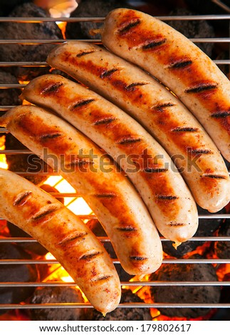 Row of tasty browned seared pork and beef sausages cooking over the hot coals on a barbecue fire, close up overhead view - stock photo