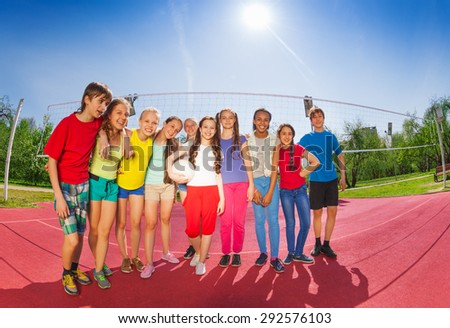 Row of teenagers who stand on volleyball court - stock photo
