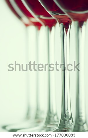 Row of the wine glasses on green light. Selective focus - stock photo