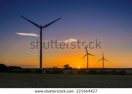 Row of three wind turbines at sunset near Lynemouth, England - stock photo