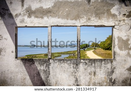 Row of three windows in a damaged white wall showing a landscape - stock photo