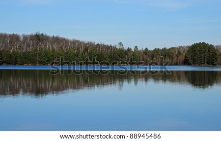 Row of trees and blue sky reflected in lake - stock photo