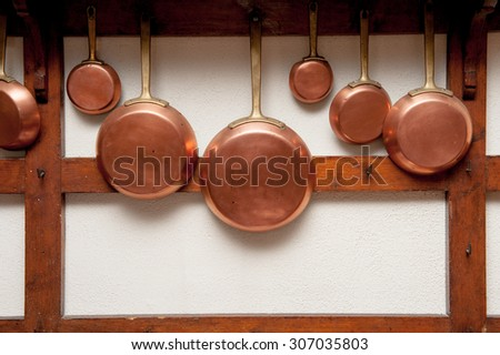 Row of vintage copper pans, different size, hung on wooden shelf in kitchen, vertical frame - stock photo