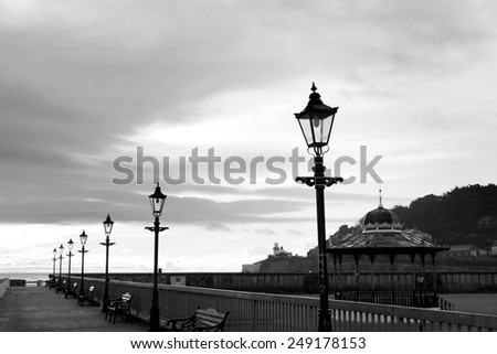 row of vintage lamps on the promenade in Youghal county Cork Ireland in black and white - stock photo