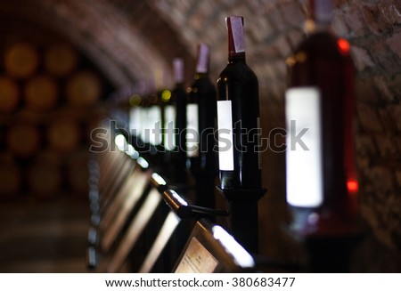 Row of vintage wine bottles in a wine cellar  - stock photo