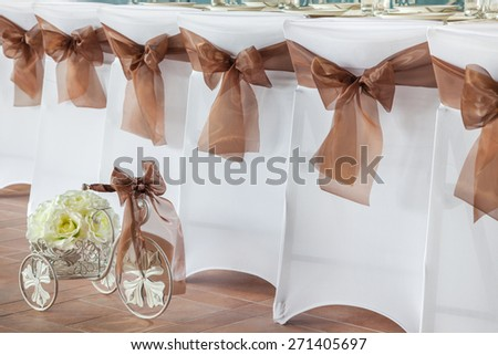 Row of wedding chairs with brown ribbons. - stock photo
