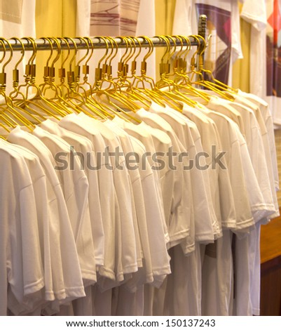 row of white shirts hanging on - stock photo