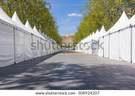 row of white tents on an empty Street among trees - stock photo