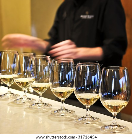 Row of white wine glasses in winery tasting event - stock photo