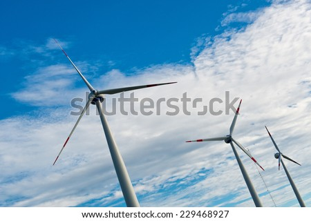 Row of wind turbines on a wind farm generating, sustainable renewable energy and electricity from the kinetic energy of the wind against a cloudy blue sky - stock photo