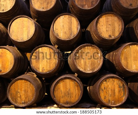 Row of wooden barrels of tawny portwine in cellar, Porto, Portugal - stock photo