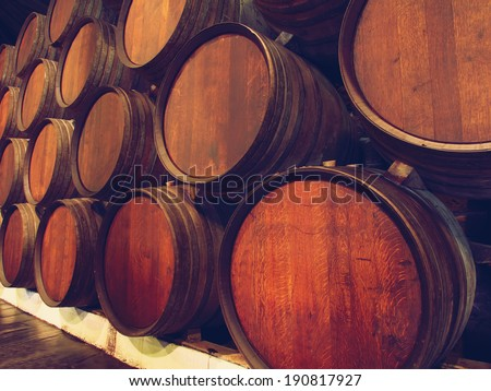Row of wooden barrels of tawny portwine ( port wine ) in cellar, Porto, Portugal. Vintage old style - stock photo