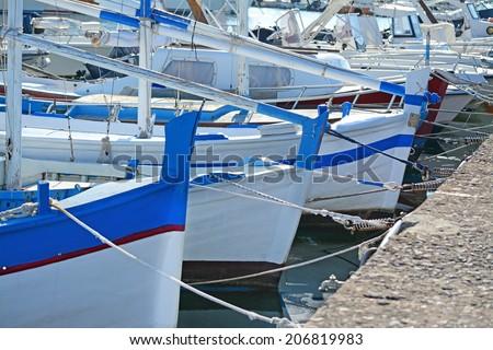 row of wooden boats in Alghero harbor - stock photo