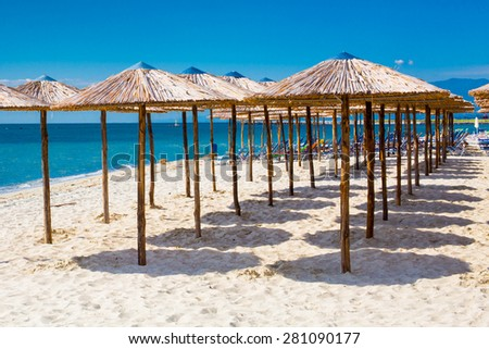 Row of wooden umbrellas at sandy beach, sea and blue sky - stock photo