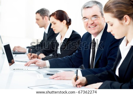 Row of working business people with focus on a senior  businessman - stock photo