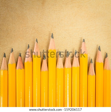 Row pencil on brown paper background - stock photo