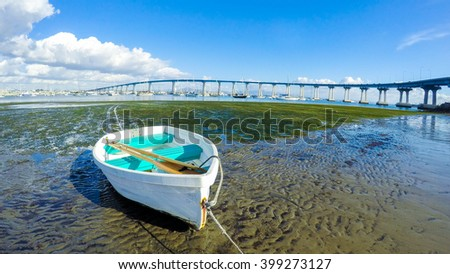 Rowboat and a blue sky on the beach - stock photo