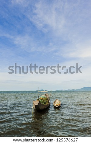 Rowboat on the blue water with background of blue cloudy sky - stock photo