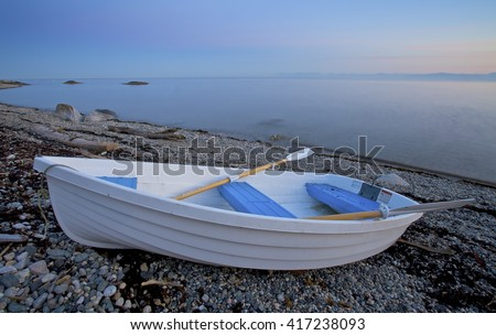 Rowboat resting on a secluded beach of the Sunshine Coast of British Columbia. - stock photo