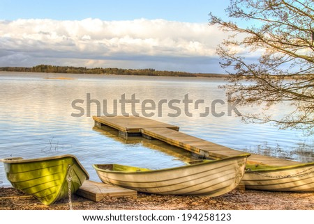 Rowboats and a pier by the lake under the low clouds - stock photo