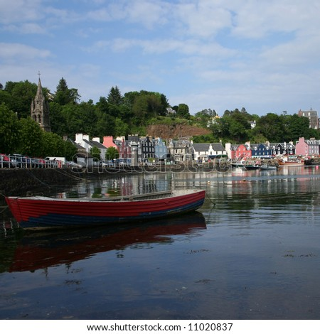 Rowing boat in tobermory harbour with colourful houses Mull Scotland - stock photo