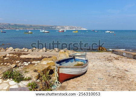 Rowing boat Swanage bay and coast Dorset England UK with blue sea and sky on a beautiful summer day on the English Jurassic coast - stock photo