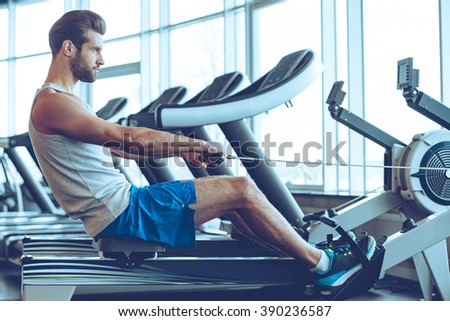 Rowing with power. Side view of young man in sportswear doing rowing in front of window at gym - stock photo