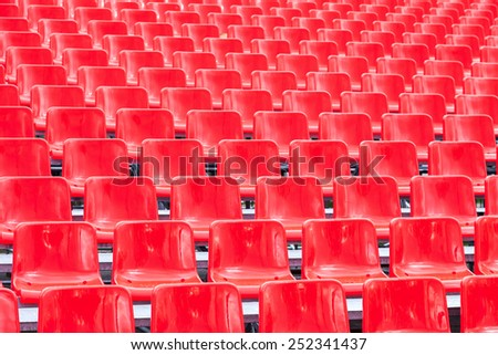 Rows empty bright red plastic seats in a stadium - stock photo