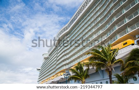 Rows of balconies on a large luxury cruise ship docked at a tropical port - stock photo