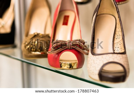 Rows of beautiful, elegant, colored women's shoes on store shelves. - stock photo