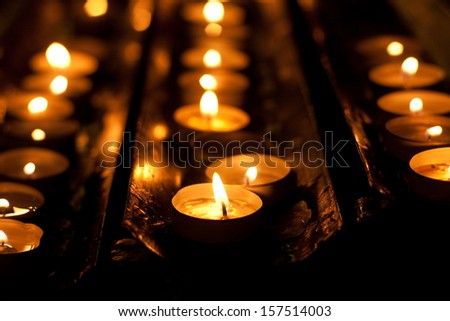 Rows of brightly burning votive candles - stock photo