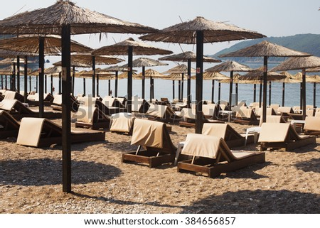 Rows of brown wooden lounge chairs and straw beach umbrellas on sea beach in the morning. Budva, Montenegro - stock photo