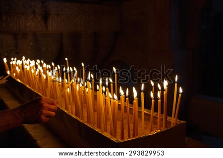 Rows of burning candles in a dim church . - stock photo