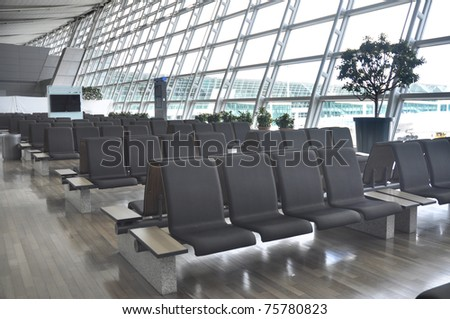 rows of chairs at an empty airport terminal - stock photo