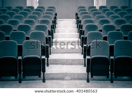 rows of chairs in auditorium in dark blue tone - stock photo