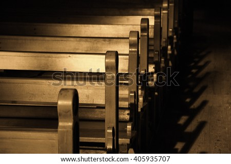 Rows of church benches. Sunlight filtered through the stained glass window. Selective focus. Sepia photo. - stock photo